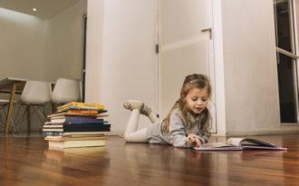 Jente som leser bok på gulvet